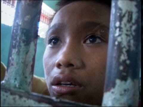 plight of boy prisoners one boy's story file / tx manila shots 13yearold boy edwin looking through bars of prison cell - philippines stock videos & royalty-free footage