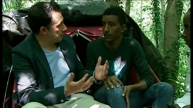 vídeos de stock e filmes b-roll de plight of migrants in calais trying to reach the uk; t05081430 / tx 5.8.2014 washing hanging on line at illegal camp for migrants reporter asking... - making money