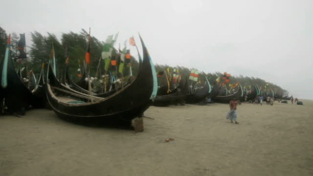 plight of muslim rohingya refugees bangladesh shamlapur camp ext boats on beach ragged flags blowing in strong wind shacks seen through trees woman... - rohingya culture stock videos and b-roll footage