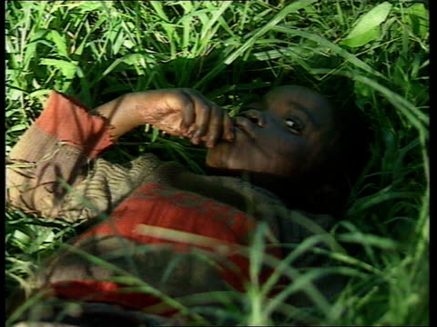 vidéos et rushes de plight of orphans tcms young boy lying on back in grass with hand in his mouth tx - orphelin