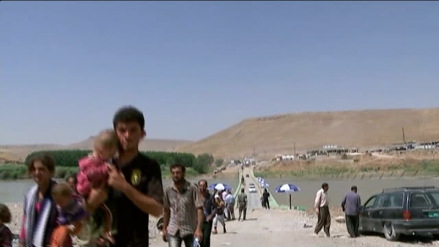 plight of yazidi people trapped on mount sinjar / helicopter carrying aid crashes; syria-iraq border: ext yazidi men along carrying sacks on heads... - isis beheading stock-videos und b-roll-filmmaterial