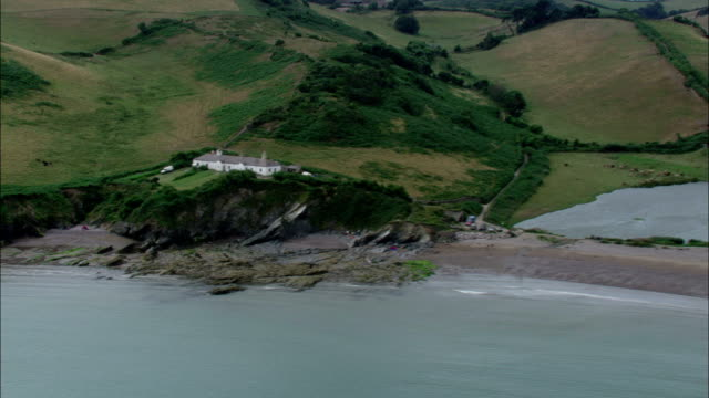 Plots of farmland border a section of the southwest coast of England. Available in HD.
