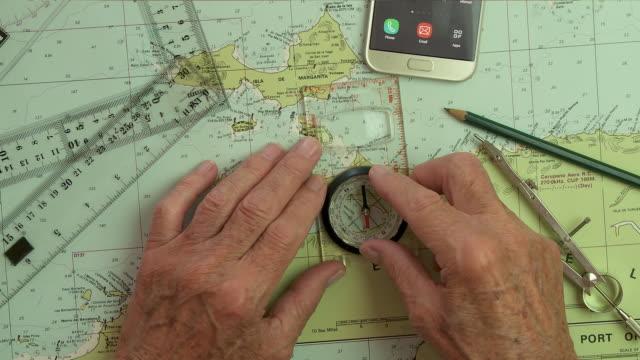 vidéos et rushes de plotting a sailing course with chart and compass - boussole