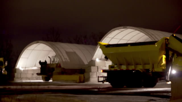 a plow passes in front of a few shelters that contains salt and calcium - salt mineral stock videos & royalty-free footage