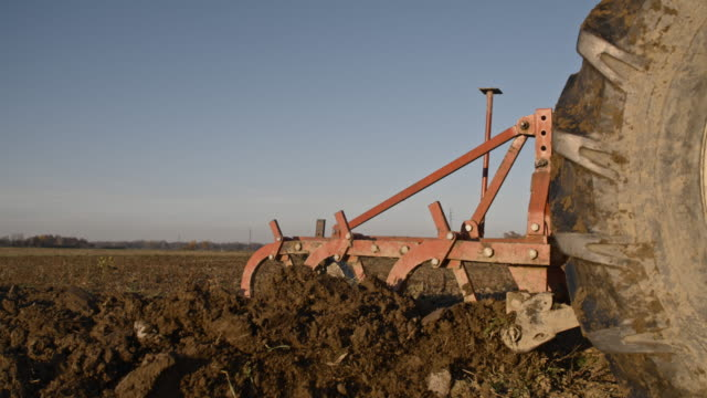 slo mo plow turning over the soil - tractor stock videos & royalty-free footage