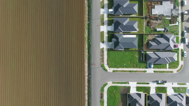 plowed field next to houses under construction - pflug stock-videos und b-roll-filmmaterial
