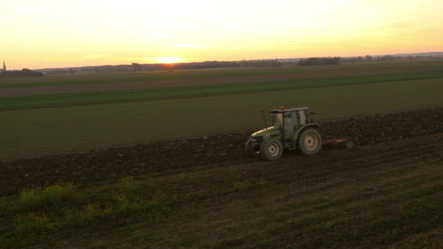 AERIAL Plowing a field with the tractor