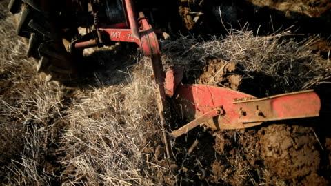 vídeos y material grabado en eventos de stock de arar de cerca. hombre mayor conduciendo tractor pequeño y la actividad de arado field. agricultural - arar