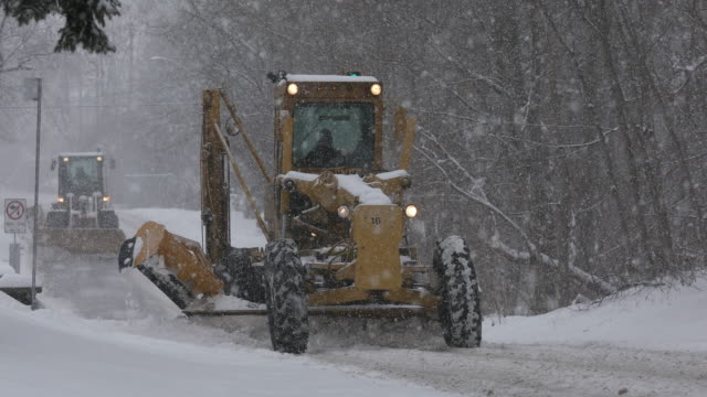 Plows clear a snow covered road
