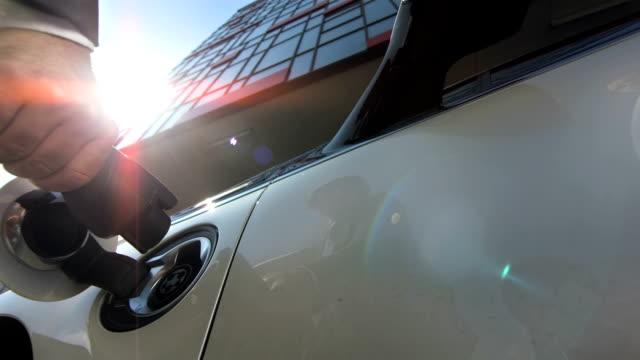 vídeos de stock, filmes e b-roll de hd câmera lenta: conectando um carro elétrico - carregamento eletricidade