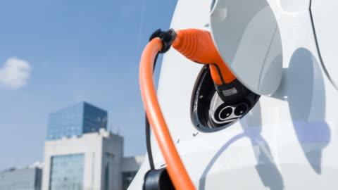 vídeos y material grabado en eventos de stock de enchufar en el coche eléctrico a la carga en un vehículo eléctrico en el centro de la ciudad - coche híbrido