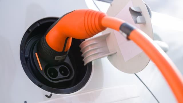 vídeos de stock, filmes e b-roll de conectar o cabo de força ao veículo elétrico para recarregar baterias - carregamento eletricidade