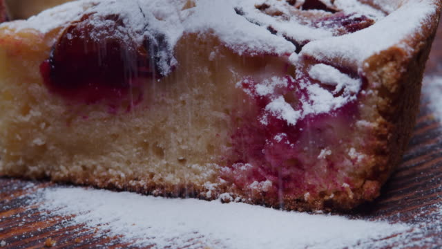 plum pie being sprinkled with powdered sugar. close-up - plum stock videos & royalty-free footage