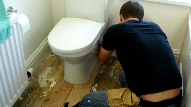Plumber fixing a Toilet in the Bathroom