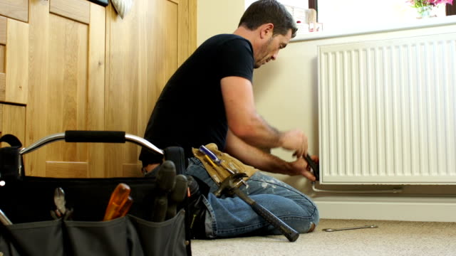 dolly hd - plumber fixing radiator in house - repairing stock videos and b-roll footage