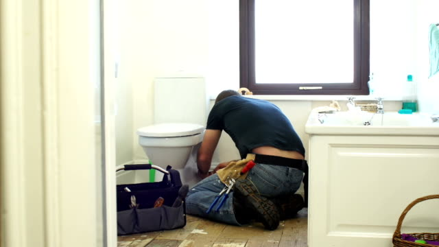 hd dolly: plumber / handyman fixing the toilet in bathroom - repairing stock videos and b-roll footage