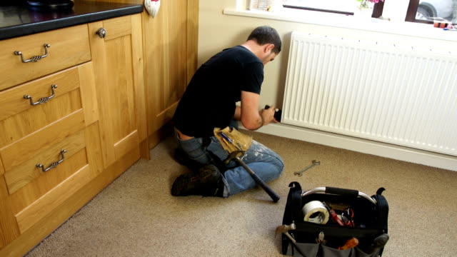 hd crane: plumber repairing radiator in house kitchen - plumber stock videos and b-roll footage