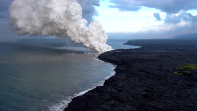 a plume of steam rises from a hawaiian coastline. - hawaii islands stock videos & royalty-free footage
