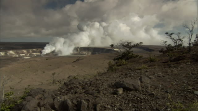 a plume of steam rises out of a crater. - shrubland stock videos & royalty-free footage