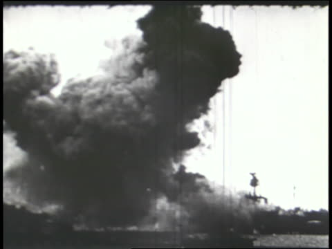 plumes of smoke fill the air as the japanese bomb pearl harbor. - sprengkörper stock-videos und b-roll-filmmaterial