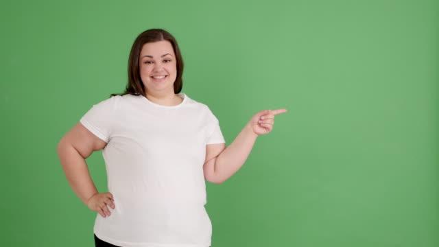 vídeos y material grabado en eventos de stock de chica regordeta muestra copia espacio en pantalla verde - camiseta blanca
