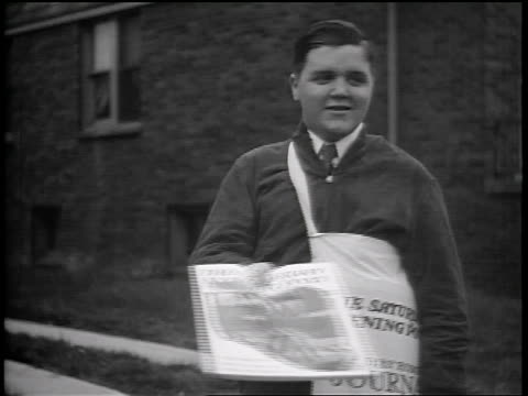 b/w 1935 plump newsboy selling saturday evening post on street / industrial - one teenage boy only stock videos and b-roll footage