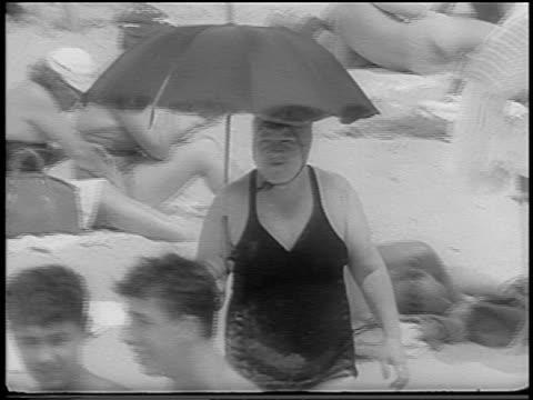 b/w 1966 plump woman in swimsuit walking on crowded beach with umbrella / newsreel - dicke frauen am strand stock-videos und b-roll-filmmaterial