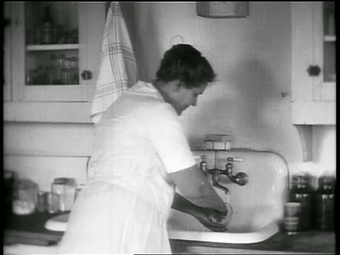 b/w 1928 plump woman washing dishes at sink / oklahoma / newsreel - 1928 stock videos & royalty-free footage