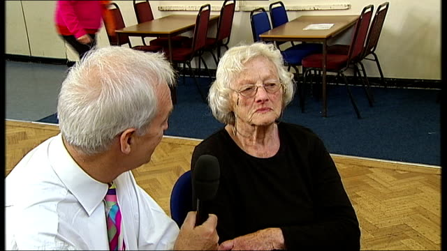 '50 plus' fitness aerobics class elderly people doing aerobic exercises in hall watched by reporter including reporter joinging in and balancing on... - on one leg stock videos & royalty-free footage