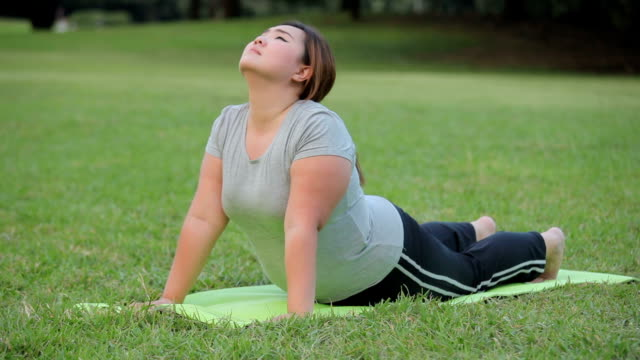 plus size asian woman practicing yoga on green grass in the park - overweight yoga stock videos & royalty-free footage