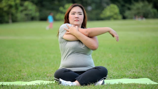 plus size asian woman practicing yoga on green grass in the park - overweight active stock videos & royalty-free footage