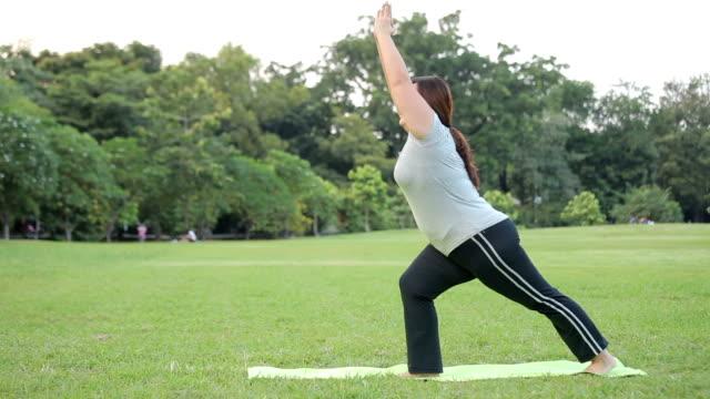 プラスのサイズのアジア女性が公園で緑の芝生の上でヨガの練習 - 大柄点の映像素材/bロール