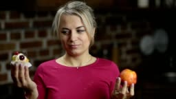 Plus size woman choosing between apple and cake