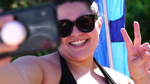 Plus Size Woman Taking a Selfie at the beach