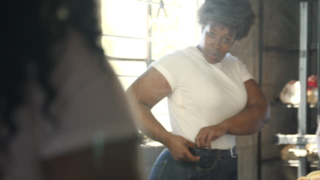 vídeos de stock e filmes b-roll de plus size women getting ready in front of a dressing room mirror - calças de ganga