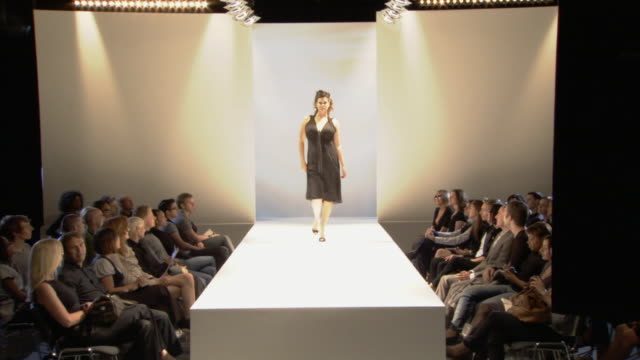 WS Plus-size woman modeling black dress on catwalk while audience watches / London, England, UK