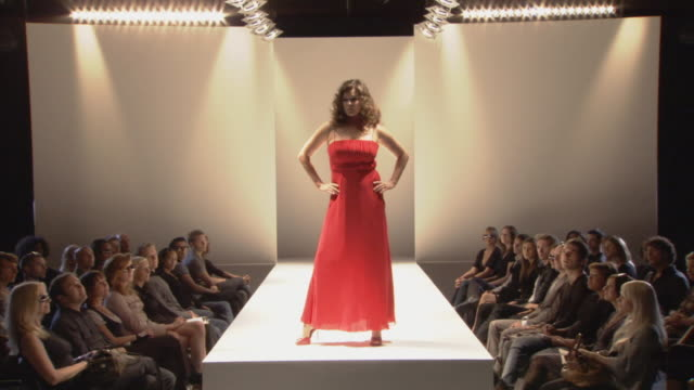 ws plus-size woman modeling red gown and posing on catwalk while audience watches / london, england, uk - fashion show点の映像素材/bロール
