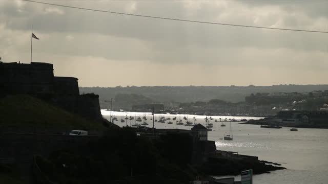 plymouth coastline at dusk, flag in distance at half mast due to mass shooting in keyham - twilight stock videos & royalty-free footage