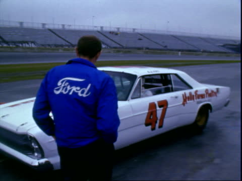 plymouth convertible daytona 500 pace car parked near racetrack daytona international speedway / mechanics kneeling near front end of 427 v8 1966... - 1966 stock-videos und b-roll-filmmaterial