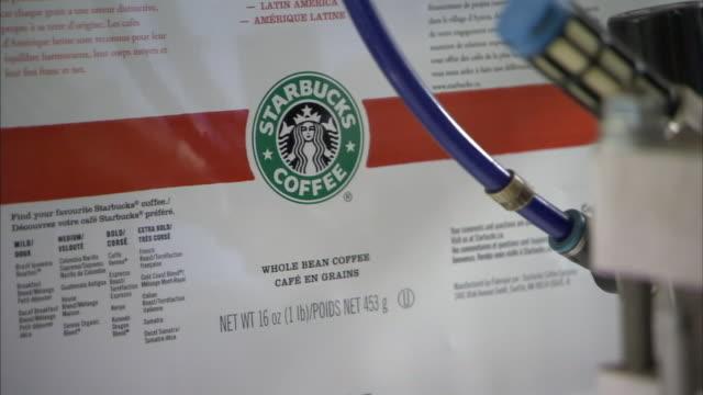 a pneumatic tube leads to a starbucks coffee label machine. - スターバックス点の映像素材/bロール