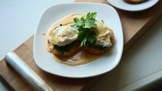 poached eggs for breakfast - hollandaise sauce stock videos and b-roll footage