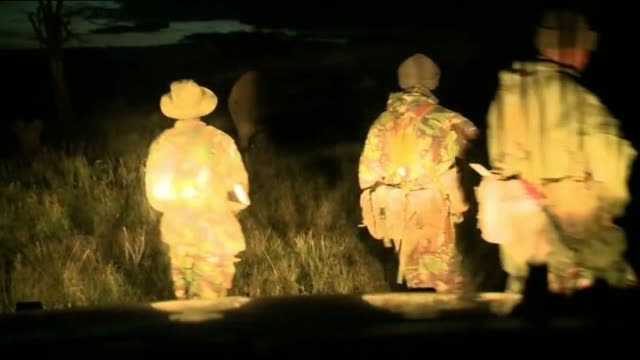 Poaching problem in Lewa National Park KENYA Lewa National Park Armed antipoaching rangers patrol on foot at night Armed rangers along in headlights...