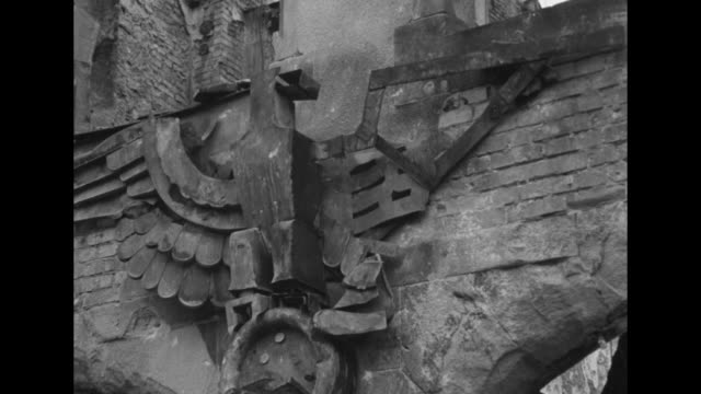pockmarked wall underneath swastika with sculpted eagle behind / partially destroyed sculpture of another stone eagle / damaged framed portrait of... - nazi swastika stock videos & royalty-free footage