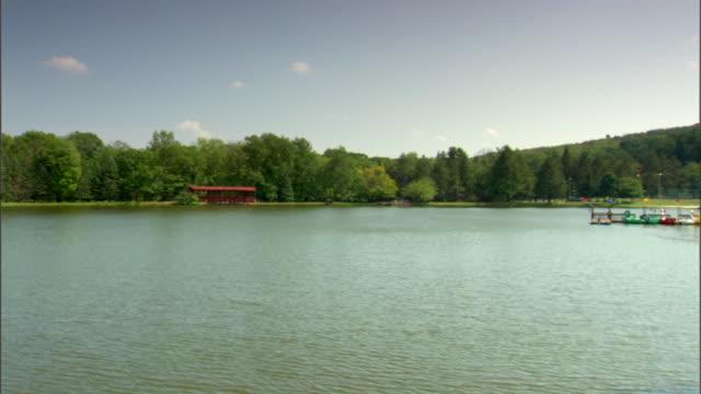 pocono mountains recreational lake w/ people in small boat near shore dock w/ shaped pedal boats docked bg - poconobergen bildbanksvideor och videomaterial från bakom kulisserna