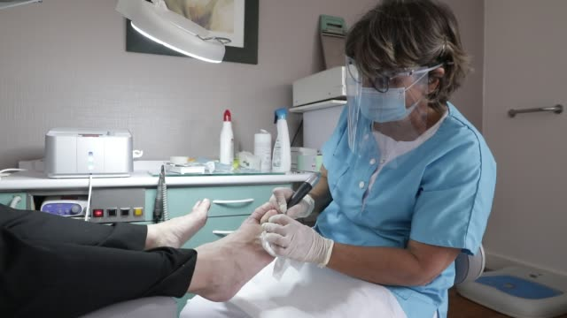 podiatrist, who is back to work, performs a pedicure in their office after the lockdown period on may 14, 2020 in chambery, france. she wears a... - pedicure stock videos & royalty-free footage