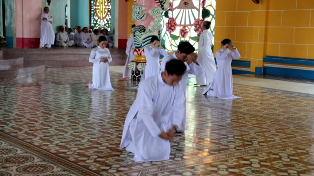 vidéos et rushes de poeple praying in the temple of cao đài religion's holy see, tây ninh, vietnam - fidèle religieux
