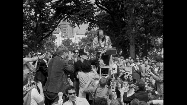 poet and writer allen ginsberg, playing an instrument and chanting, is stopped by a policeman to boos from the crowd at a hippy rally in favour of... - beatnik stock videos & royalty-free footage