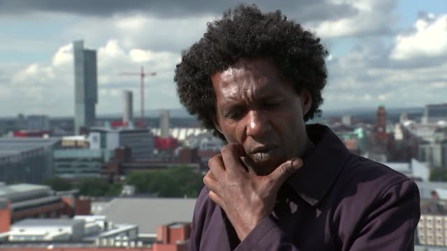 poet and writer lemn sissay talks about his life; manchester: ext lemn sissay on roof of building high angle shot of tops of buildings and clock lemn... - butter fly stock videos & royalty-free footage