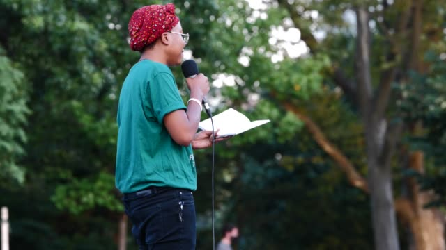 poet nathalie amazan reads during the womxn poets for black lives event on the 54th night of the george floyd vigil at mccarren park. - poet stock videos & royalty-free footage