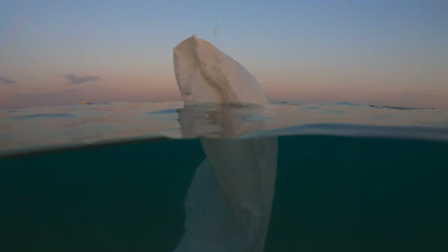 poetic view of plastic bag floating in the sea like iceberg. - obsoleto video stock e b–roll